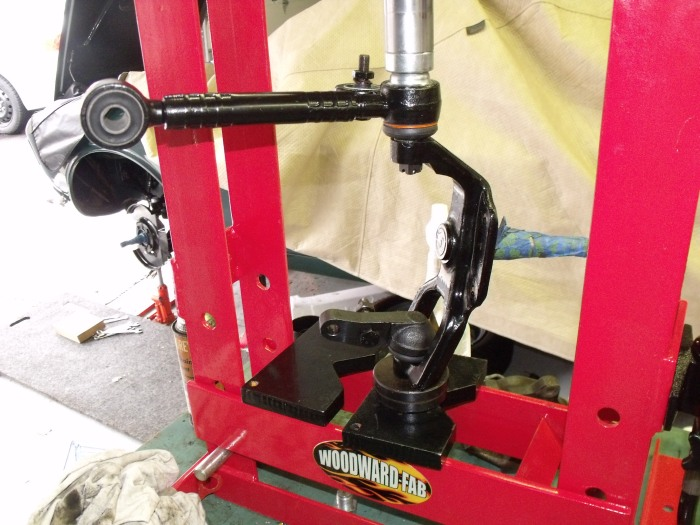 Using the bench-top press to drive home the upper control arm/ball joint into the spindle.