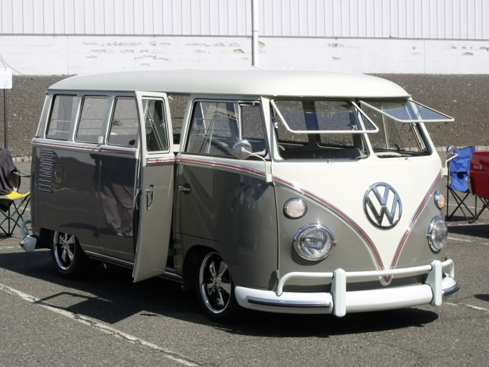 A beautifully restored VW bus, lowered and wearing Porsche wheels.