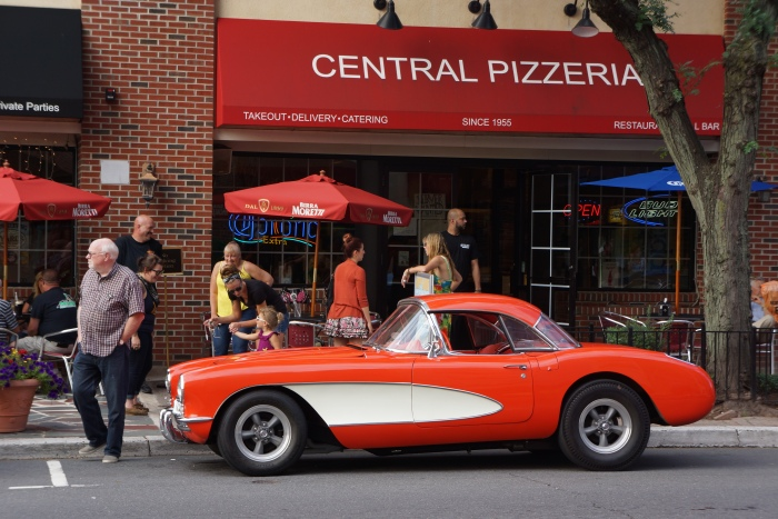 A C1 Corvette in front of a pizzeria of the same vintage