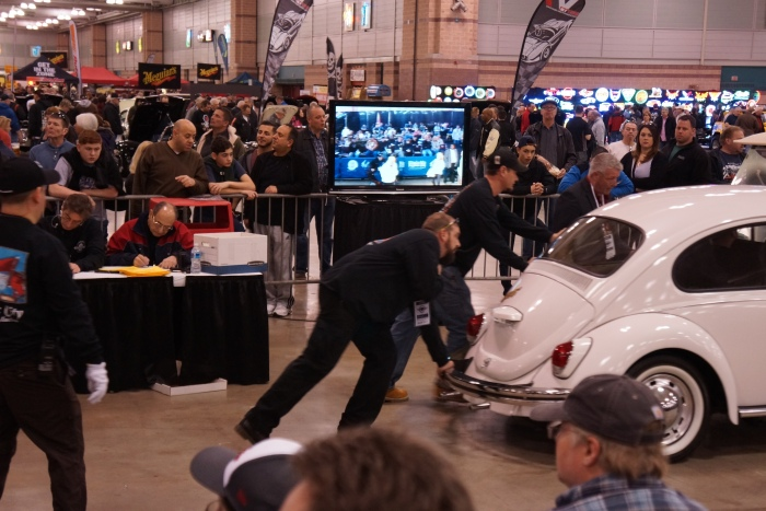 The pushers move a VW Beetle off the block an past the TV screen.