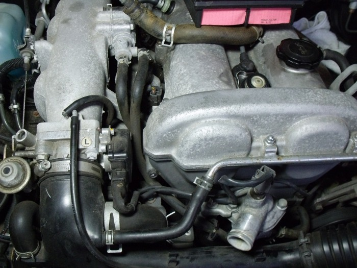 The two hoses, running parallel between intake and valve cover, are coolant hoses