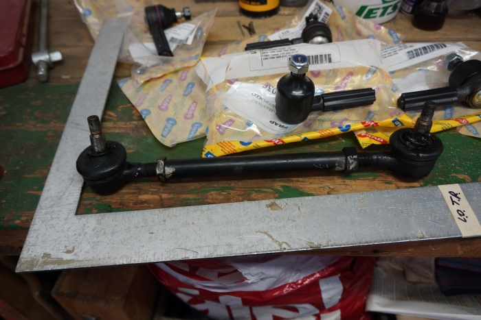 One of the tie rods is out, with parts and parts bags strewn on the bench