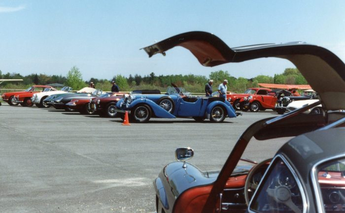 An open Gullwing door frames the parking lot
