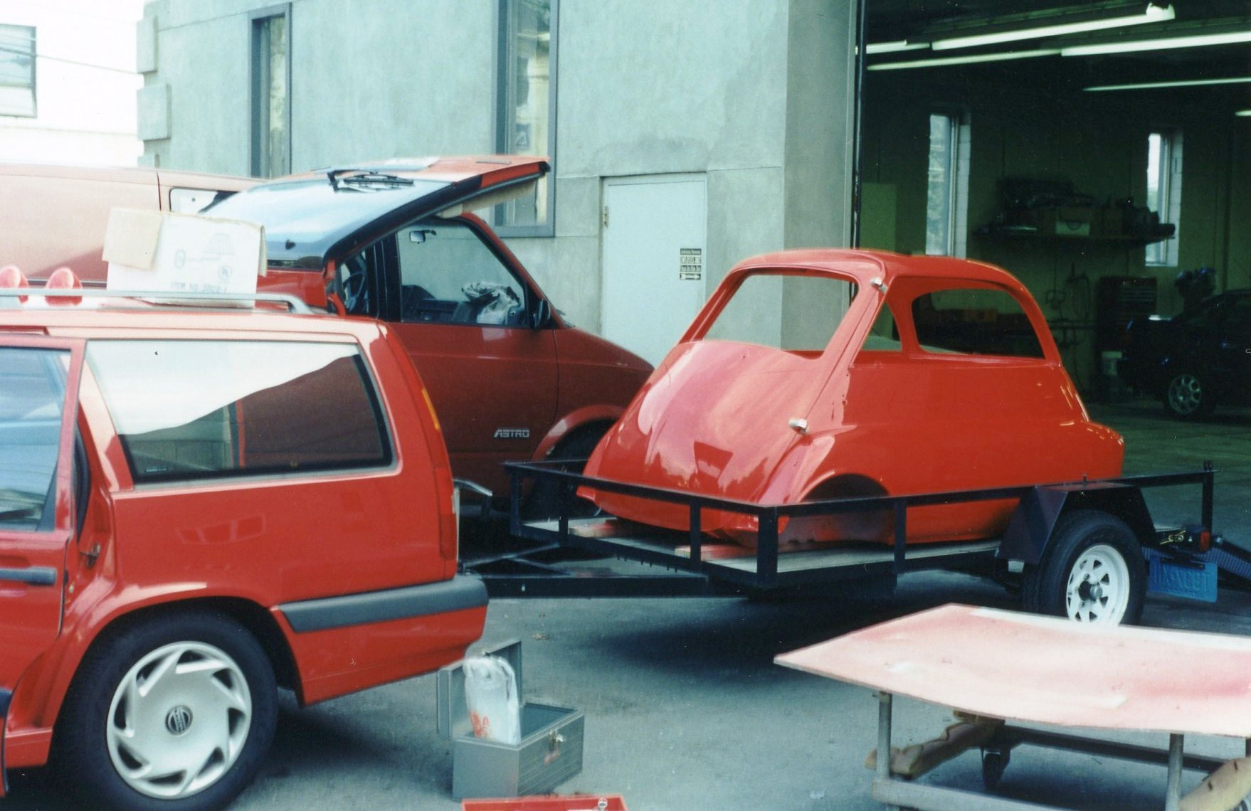 the red 850, ready to tow home the red isetta (note dolly and plywood in  lower right of photo)